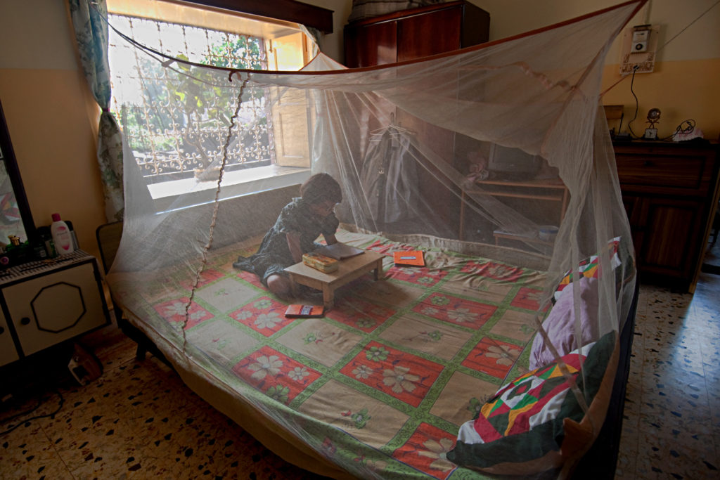 A yoA young girl reading under a malaria bednet. Photo: UNDP